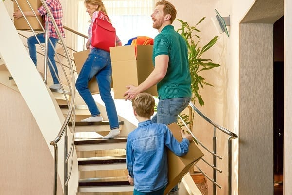 Family carrying boxes upstairs.